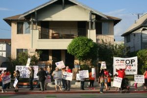 Protesters hold signs in front of one of the apartment buildings to be demolished for the construction of a 50-unit apartment building near 1st and Soto streets. Photo by Antonio Mejías-Rentas